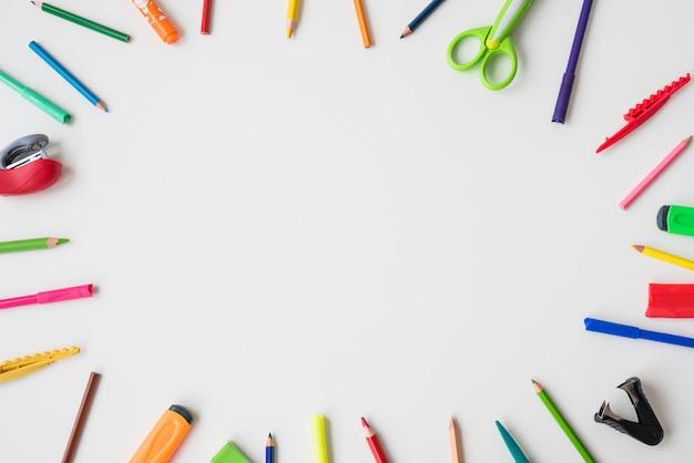 Fournitures scolaires disposées en forme circulaire sur le fond blanc Photo gratuit