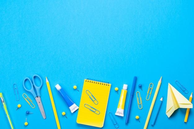 Fournitures scolaires jaunes sur le fond bleu pastel. Photo Premium