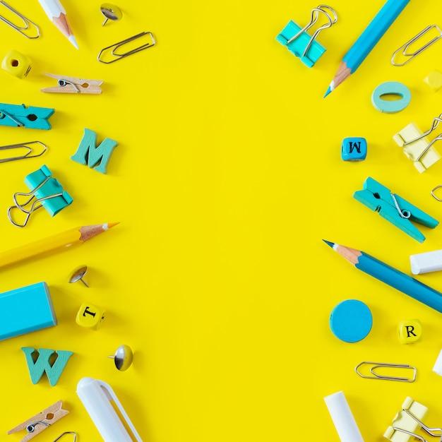 Fournitures scolaires multicolores sur fond jaune avec espace de copie. Photo Premium