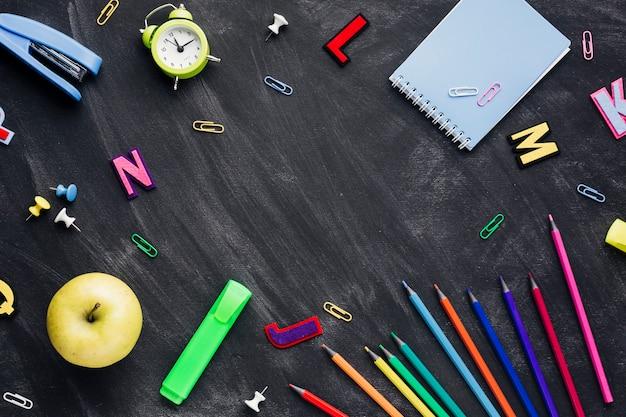 Fournitures scolaires avec pomme et réveil dispersées sur un tableau noir Photo gratuit