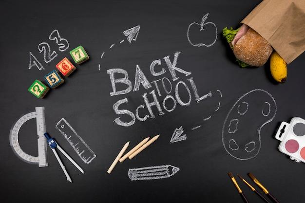 Fournitures scolaires et sandwich sur tableau noir Photo gratuit
