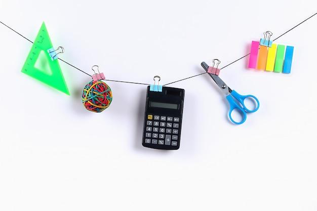 Les fournitures scolaires sont suspendues à une corde. fournitures scolaires sur blanc. concept de retour à l'école Photo Premium