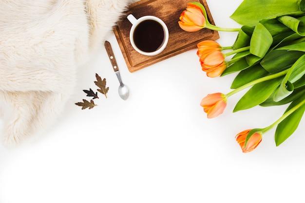 Fourrure; cuillère; tasse à café et une tulipes orange sur fond blanc Photo gratuit
