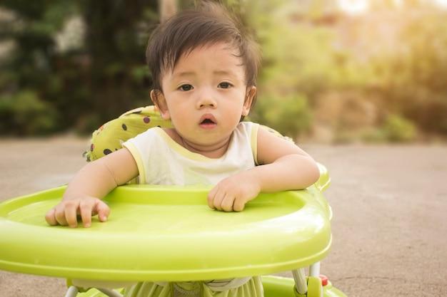 Foyer asiatique garçon assis sur une chaise de bébé Photo Premium