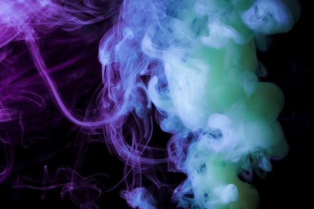 Fragments de fumée dense sur fond noir Photo gratuit
