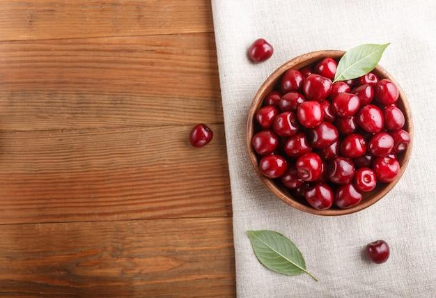 Frais cerise rouge dans un bol en bois. vue de dessus. Photo Premium