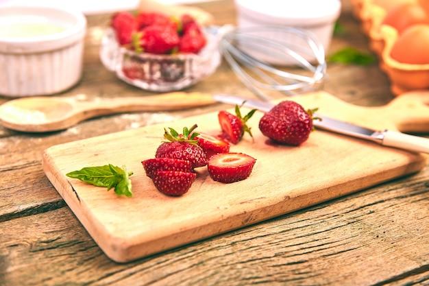 Fraise sur une planche à découper. ingrédients crus pour la cuisson de la tarte aux fraises Photo Premium