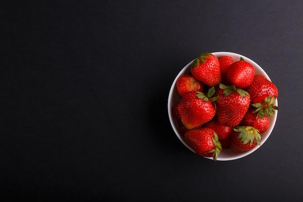 Fraise rouge fraîche dans un bol blanc sur fond noir. vue de dessus. Photo Premium