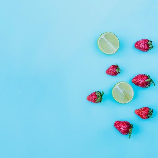 Fraises Décoratives Et Limes Sur La Surface Bleue Photo gratuit
