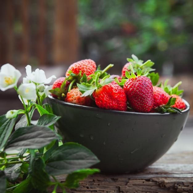 Fraises Avec Fleurs Sur Branche Dans Un Bol Sur Table En Bois Et Cour, Vue Latérale. Photo gratuit