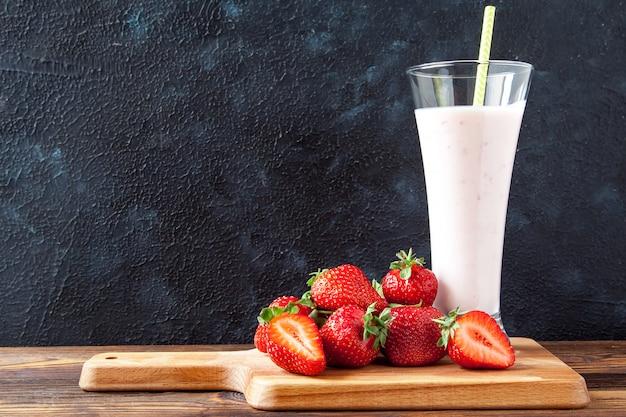 Fraises fraîches sur une planche de bois et du yaourt avec des tranches de fraises dans un verre sur une table en bois sur un fond noir Photo Premium