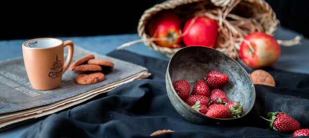 Fraises à l'intérieur du bol, biscuits, tasse et panier de pommes sur un tapis noir. Photo gratuit