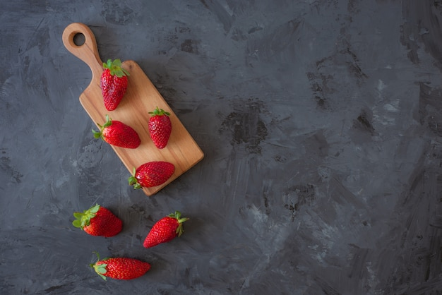 Fraises rouges sur une plaque en bois sur fond noir, vue de dessus, flatlay avec espace de copie Photo Premium