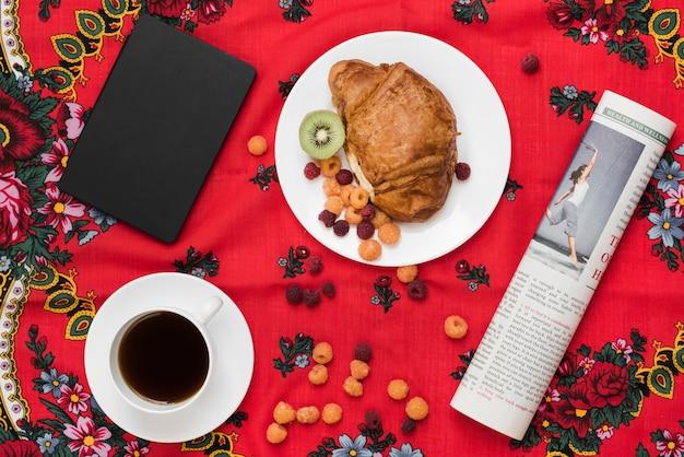 Framboise; kiwi et croissant sur une assiette avec une tasse de café; journal intime et journal enroulé sur nappe Photo gratuit