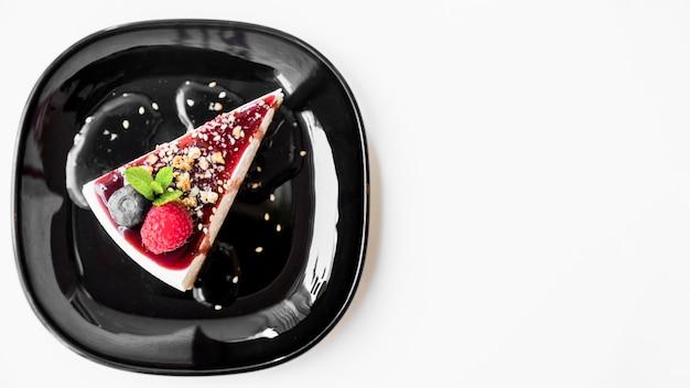 Framboise et menthe avec gâteau au fromage sur plaque noire sur fond blanc Photo gratuit