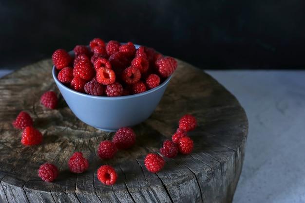 Framboises Sucrées Et Saines Dans Une Assiette En Verre Sur Un Fond En Bois Photo Premium
