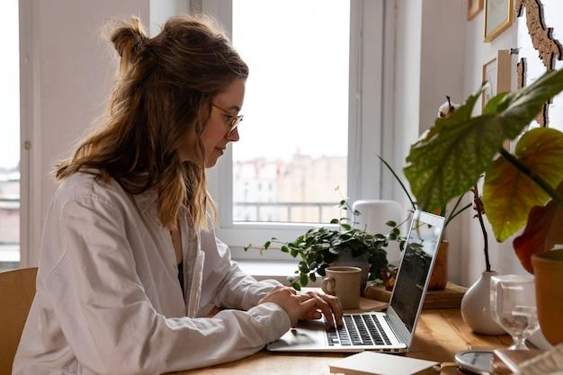 Freelance / Designer Femme Travaillant Sur Ordinateur à Domicile. Lieu De Travail Confortable Entouré De Plantes. Travail à Distance Photo Premium