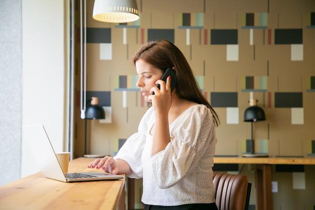 Freelance Féminine Focalisée Travaillant Sur Un Ordinateur Portable Et Parlant Au Téléphone Portable Dans Un Espace De Travail Collaboratif Photo gratuit