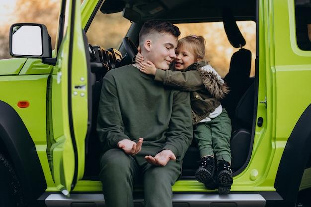 Frère avec petite soeur assis dans la voiture verte Photo gratuit