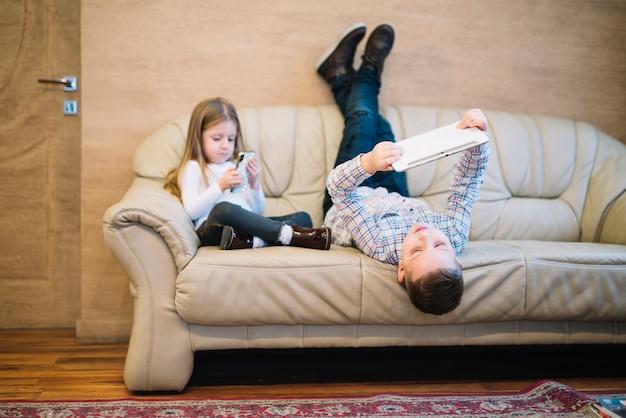 Frère et soeur assis sur un canapé à l'aide d'un téléphone portable et d'une tablette numérique Photo gratuit