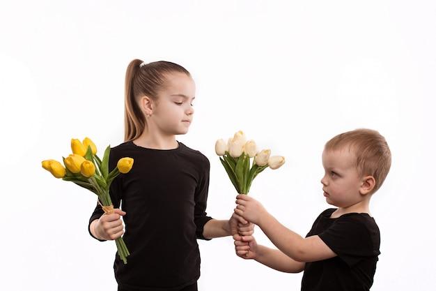 Frère Et Soeur En Blouse Noire Tenant Des Tulipes Dans Leurs Mains Photo Premium