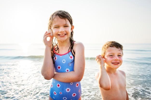 Frère et soeur profitant de la plage Photo gratuit
