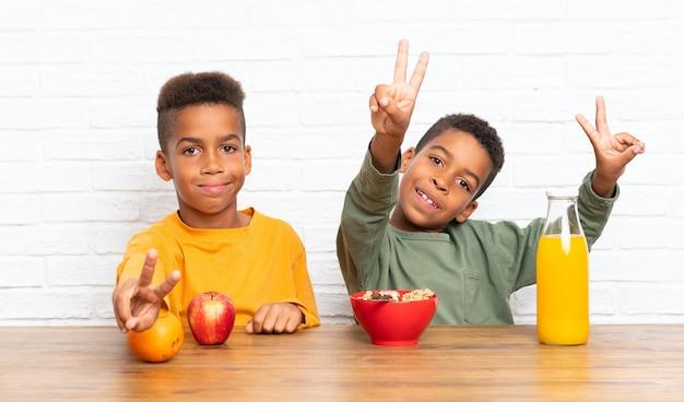 Frères afro-américains prenant son petit déjeuner et faisant le geste de la victoire Photo Premium