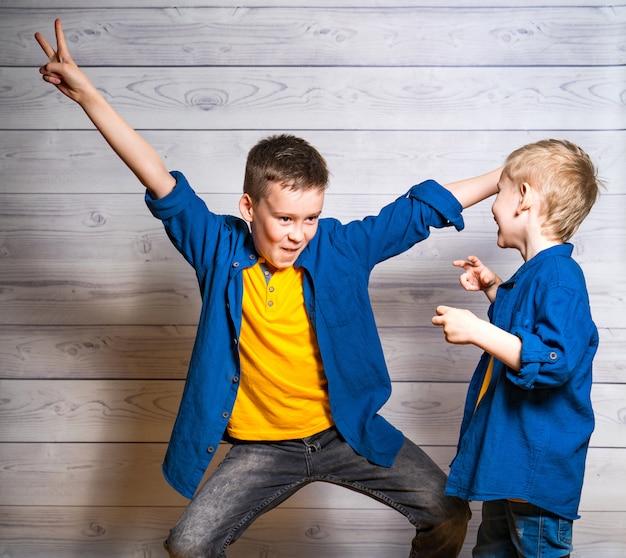 Frères heureux et amicaux pendant le match. un garçon aîné montre une pose amusante et un autre plus petit se moque de lui avec joie. deux amis émotifs et positifs. Photo Premium