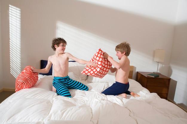 Des frères à la poitrine nue, des logements rudes et des oreillers dans un lit dans la chambre Photo Premium