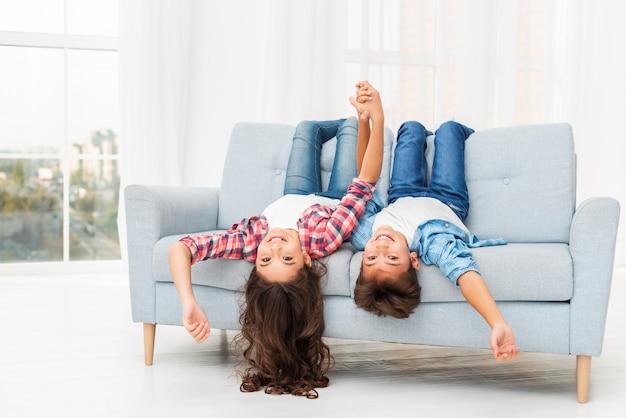 Frères et sœurs sur le bord du canapé avec la tête pendante Photo gratuit