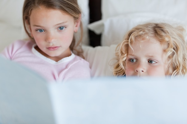 Frères et sœurs lisant une histoire au coucher Photo Premium