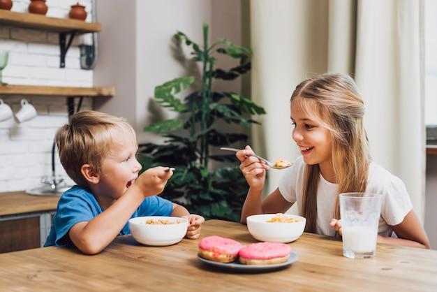 Frères et sœurs mangeant ensemble dans la cuisine Photo gratuit
