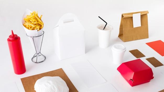 Des frites avec des aliments emballés; bouteille de sauce et tasse d'élimination sur fond blanc Photo gratuit