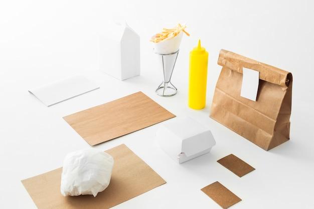 Frites; bouteille de sauce et colis de nourriture sur fond blanc Photo gratuit