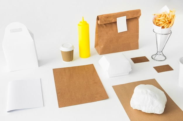 Frites; bouteille de sauce; gobelet et colis sur une surface blanche Photo gratuit