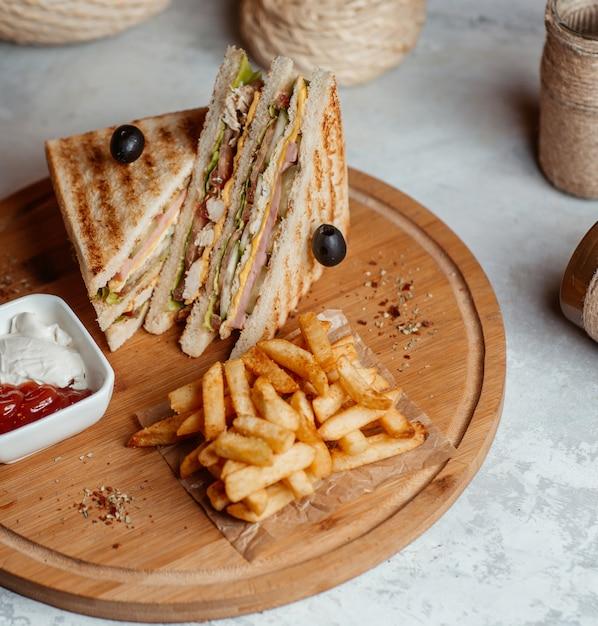 Frites avec des clubs sandwichs servis avec des sauces sur une planche de bois Photo gratuit