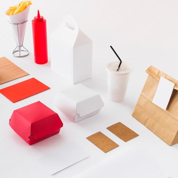 Frites; coupe d'élimination; bouteille de sauce et colis de nourriture sur la surface blanche Photo gratuit
