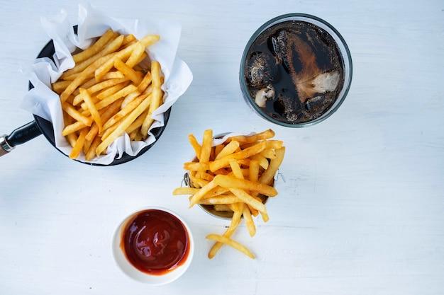 Frites Frites Et Ketchup Avec Des Boissons Gazeuses Sur Une Table Photo Premium