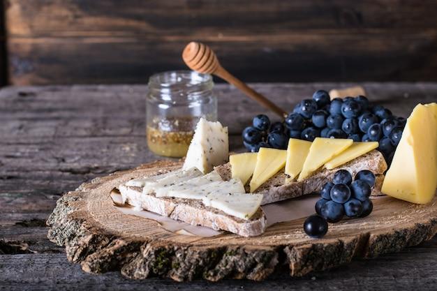 Fromage aux raisins, pain, miel. fromage de chèvre aux herbes. planche de bois naturelle. Photo Premium