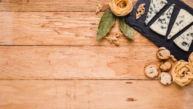 Fromage bleu; pain; pâtes et feuilles de laurier sur pierre noire sur le plan de travail avec espace pour le texte Photo gratuit