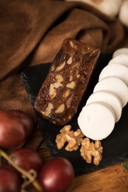 Fromage brun et blanc avec noix et raisins sur ardoise noire Photo gratuit