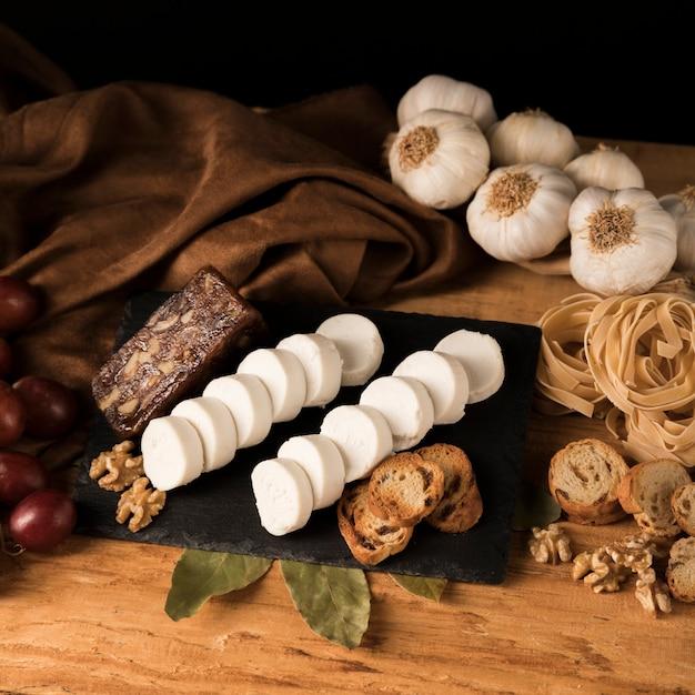 Fromage de chèvre frais sur un plateau en ardoise avec tranches de pain et noix près des pâtes crues et des bulbes d'ail Photo gratuit
