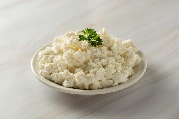Fromage cottage sur fond de marbre. produits laitiers, calcium et protéines. Photo Premium