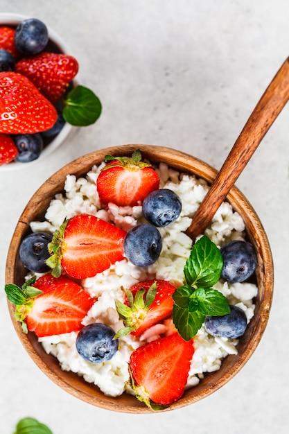 Fromage cottage avec des fraises et des bleuets dans un bol en bois Photo Premium