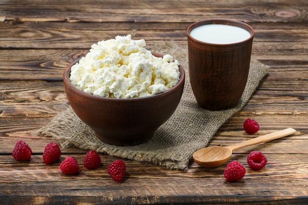 Fromage cottage et lait en terre cuite sur une table en bois Photo Premium