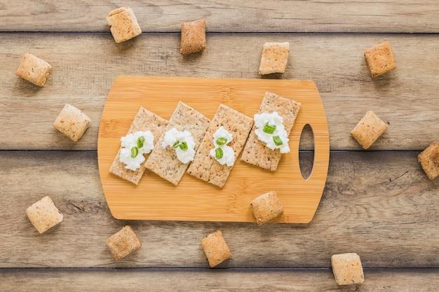 Fromage à la crème fraîche sur du pain croustillant sur la planche à découper du bureau Photo gratuit