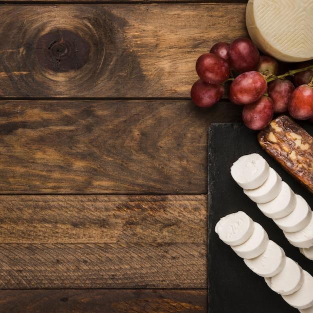 Fromage éclatant et raisins rouges sur une surface en bois sale Photo gratuit