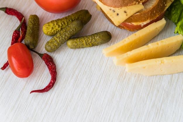 Fromage frais près des tomates, des concombres et des poivrons rouges Photo gratuit