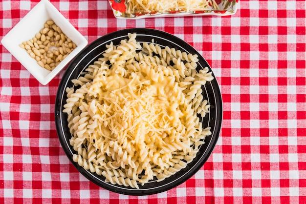 Fromage sur des pâtes fraîches près d'une assiette avec des noix sur la table Photo gratuit