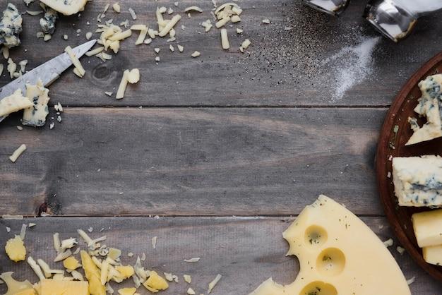 Fromage râpé et des tranches sur un bureau en bois gris pour écrire le texte Photo gratuit